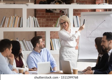 Middle aged friendly business coach lead corporate training teach diverse company young staff showing statistics using flip chart, pointing raised chart positive forecast to corporate clients concept