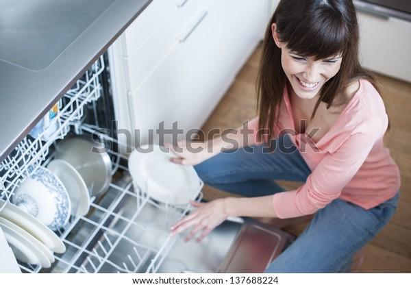 Mädchen mittleren Alters in der Küche mit Geschirrspüler.  Blick auf junge Frau in der Küche, die Hausarbeit macht