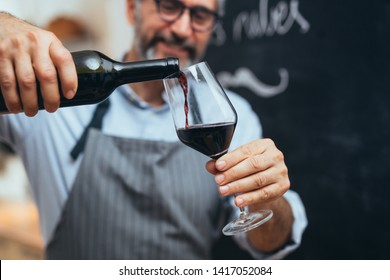 middle aged gray haired bearded filling wineglass with red wine in his home kitchen
