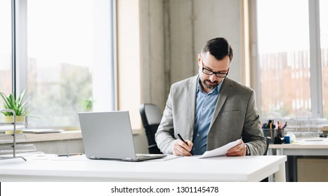 Middle aged handsome businessman in shirt working on laptop computer in office. Man working in office