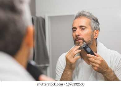 middle aged handsome man trimming his beard in bathroom