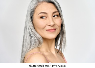 Middle aged happy mature asian woman, senior 50 year lady looking away, isolated on white closeup headshot. Ads of antiaging uv protection whitening menopause dry skincare, plastic surgery.