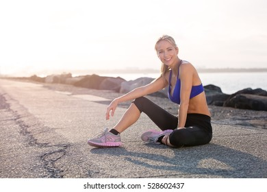 Middle aged healthy woman relaxing and happy after her fitness exercise. She is smiling and looking at the camera with sunset in the background. Gold Coast Australia.