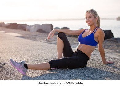 Middle aged healthy woman relaxing and happy after her fitness exercise. She looks positive and happy with her body with the sunset in the background.
