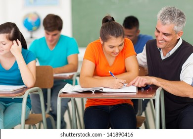 middle aged high school teacher helping a student in classroom