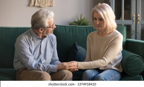 Middle aged husband holding hands, caressing sad upset wife at home, mature couple sitting on sofa, grey haired man expressing sympathy and understanding, family showing support and love