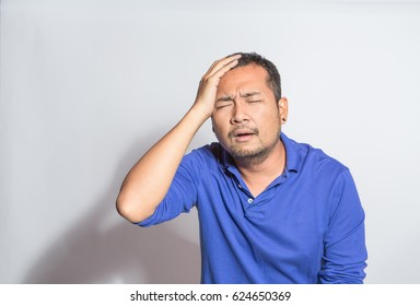 middle aged mad in blue shirt with serious headache expression, has bad mental health and too much life problems