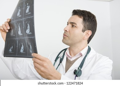 Middle aged male doctor analyzing x-ray in clinic