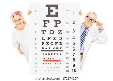 Middle aged male doctor and female patient standing behind eyesight test isolated on white background