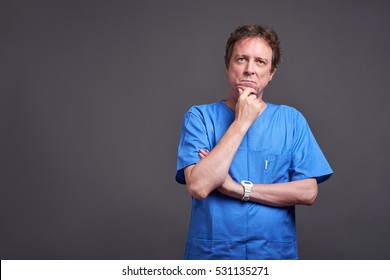 A middle aged male doctor standing and thinking in a blue scrubs.