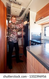 Middle aged male standing in the kitchen corner inside of recreational vehicle motor home. Travelers journey and adventure, spending time, living and traveling in camper van concept