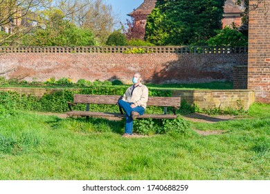 A middle aged male wearing protective face mask sitting on a bench outdoors