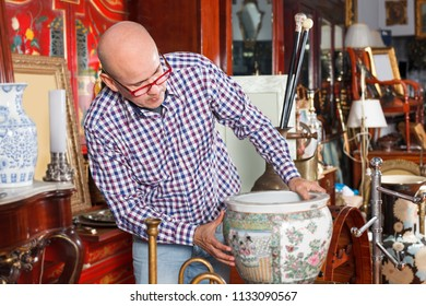 Middle aged male working in antique store, is looking at the vintage vase
