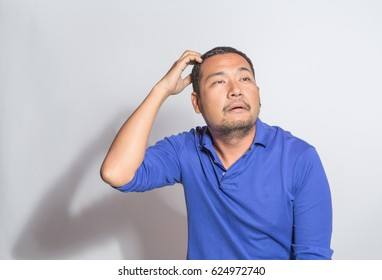 middle aged man in blue shirt scratch his head show funny muddled confuse face