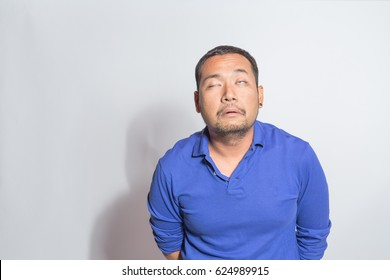 middle aged man in blue shirt half-closed his eyes with sleepy drowsy face expression, lack of sleep