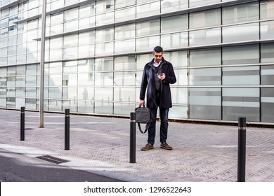 Middle aged man with a briefcase and a phone on the street