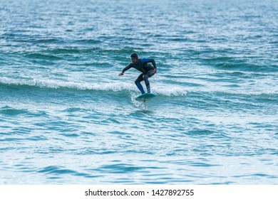 A middle aged man doing some foil surfing or hydrofoil surfing in the sea.