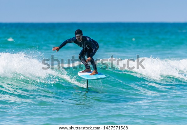 A middle aged man doing some foil surfing or hydrofoil surfing in the sea on a bright sunny day.