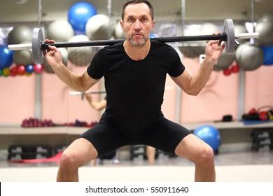 Mittlerer Mann mit großem Grillplatz im Fitnessraum