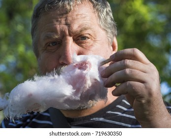 Middle aged man eating a stick of candy floss or cotton candy made from sticky spun sugar