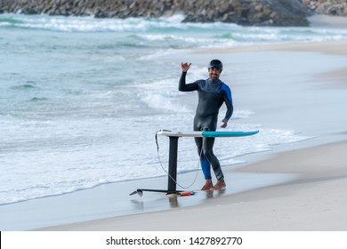 A middle aged man is finishing some foil surfing or hydrofoil surf training in the sea.