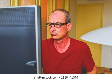 Middle aged man with glasses sitting at desk. Mature man using personal computer. Senior concept. Man working at home office