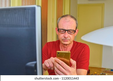 Middle aged man with glasses sitting at desk. Mature man using mobile phone. Senior concept. Man at home office