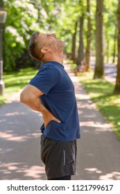 Middle aged man holding his painful back after running in park on sunny day