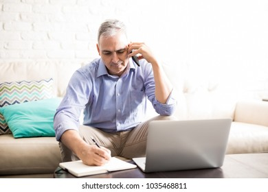Middle aged man at home making notes in diary while talking over phone