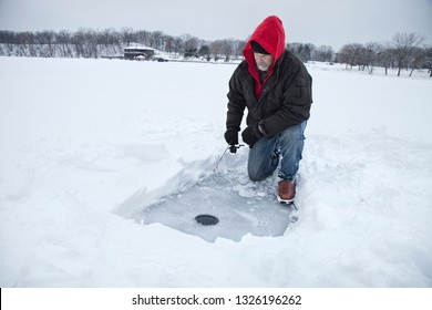 A middle aged man ice fishing on a snowy lake in Minnesota during the winter