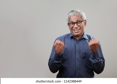 Middle aged man of Indian origin with a cheering expression