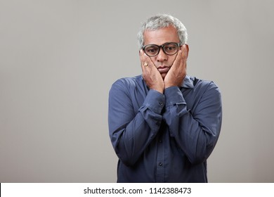 Middle aged man  of Indian origin with a worried face