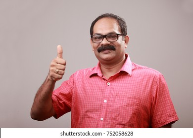 Middle aged man of Indian origin shows OK gesture