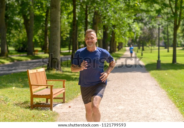 Middle aged man jogging along alley in park on sunny day in a close up view
