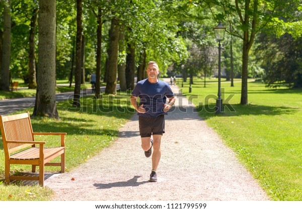 Middle aged man jogging along alley in park on sunny day