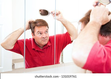 Middle aged man looking for bald spots in the mirror.