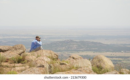 Middle aged man meditating on top of a mountain, looking across the wide open space