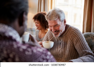 Middle Aged Man Meeting Friends Around Table In Coffee Shop