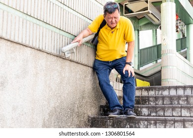 MIddle aged man with painful knee struggle walking down flight of stairs in city