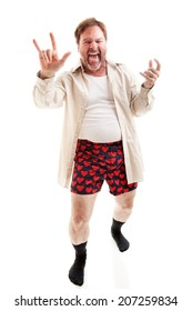 Middle aged man plays air guitar in his underwear and gives the rock-n-roll symbol.  Full body on white.