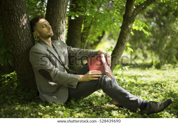middle aged man rading book in park