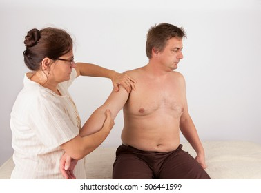 Middle aged man receives bowen massage treatment for his arms. Bowen is a holistic system of healing.