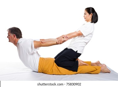 middle aged man receiving massage by therapist in traditional Thai position