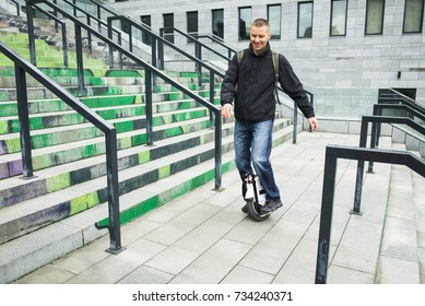 Middle aged man riding on one wheel electronic device in the city. Modern technologies for transportation. Gyroboard as a personal eco transport