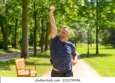 Middle aged man showing winning gesture while jogging in park on sunny day