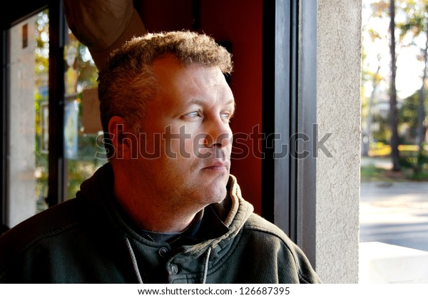 Middle aged man sitting by a window in a restaurant.