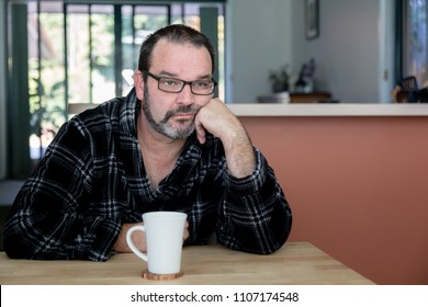 Middle aged man sitting at dining room table with coffee mug looking sad and depressed