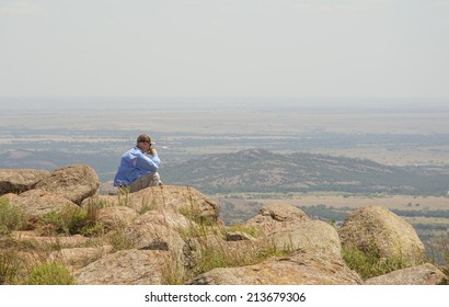 Middle aged man sitting and meditating on top of a mountain