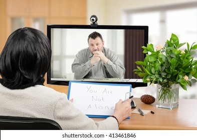 Middle aged man sitting in the monitor talks with psychotherapist via on-line video chat. He looking depressed. Black-haired psychiatrist holds written message for him You are not alone