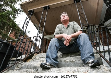 Middle aged man sitting on the steps of a house in the inner city, focus on face